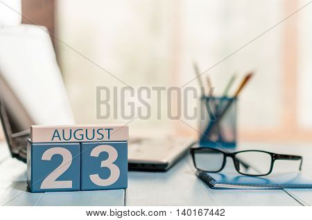 August 23rd. Day 23 of month, wooden color calendar on law office background. Summer time. Empty space for text.