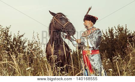 King Dressed In Medieval Costume Is Going To Stroke His Horse On The Rural Summer Background.
