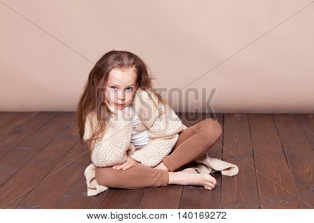 a little girl sitting on the floor and sad