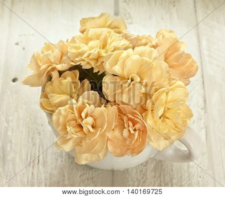 A bouquet of tender yellow carnation flowers on a light wooden boards background slightly toned