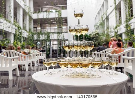 Pyramid of glasses of champagne in a large hall