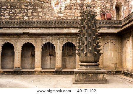 Interiors of a fort in maheshwar india showing arches in a stone wall and a carved pillar. This is a popular tourist destination