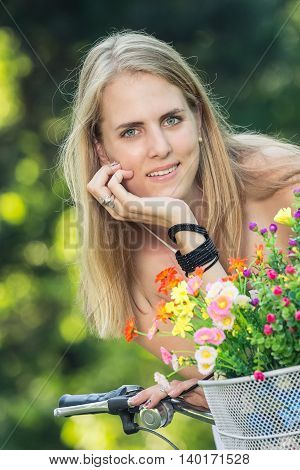 Portrait of pretty young female on bicycle with basket full of colorful flowers. Summer, nature and recreation concepts.