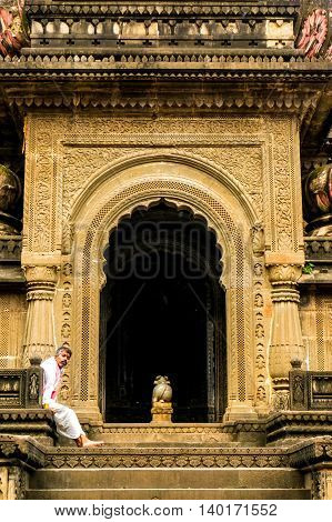 Maheshwar, India - 16th July 2016: Pundit priest sitting at the entrance of an ornate hindu temple