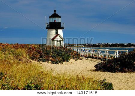 Nantucket Island Massachusetts - October 12 2008: Branch Point lighthouse capped by a single fresnel light encased in a black cupola sits on a sandy island