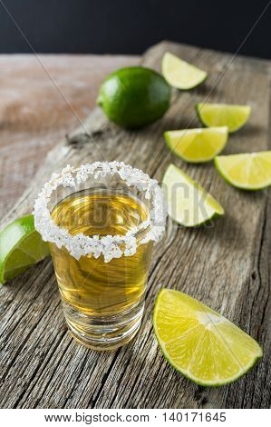 Gold tequila shot with lime slices on rustic wooden table. Gold Mexican tequila shots. Strong alcohol drink.