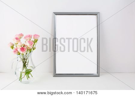 Silver frame mockup with pink roses. Portrait or poster white frame mockup. Empty white frame mockup for presentation artwork.