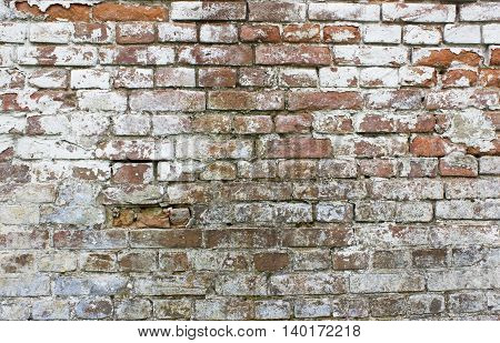 Old grungy wall with white and red bricks for background. Cracked brickwall texture.