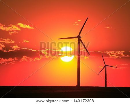 Sun bursting through the clouds at a wind farm on the plains