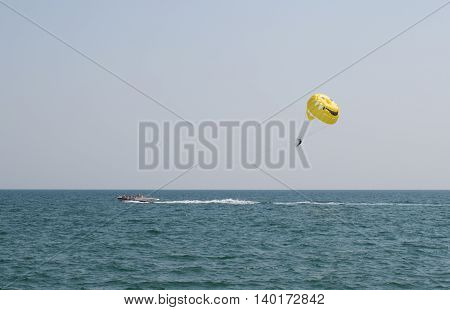 A man flying on a parachute behind the boat in the daytime