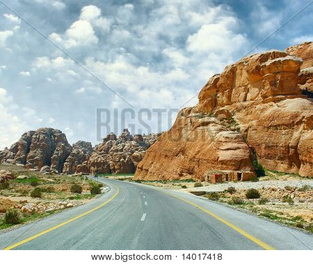 Asphalt road blue sky with clouds and mountains