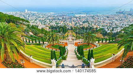 The perfectly landscaped terraced Bahai Gardens on the of Carmel Mount with the buildings of Haifa and Mediterranean coast in the distance Israel.