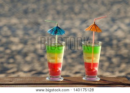 Multi-colored cocktails on a wooden table on the beach the sand on the background