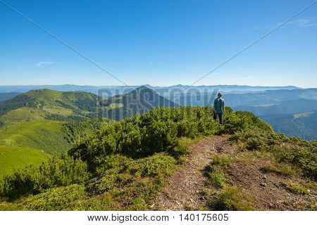 Hiker standing on mountain pass looks at the mountain tops and enjoys the beauty of nature. Ukrainian Marmarosy. Carpathians