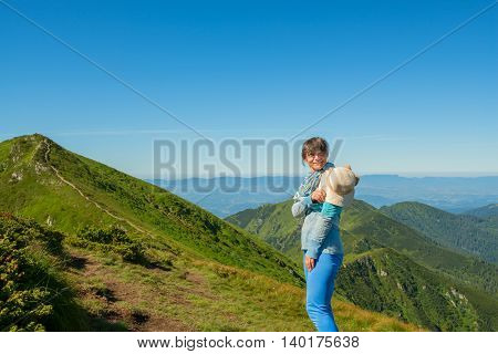 Smiling woman hiker with a straw hat in the hands resting before the ascent to the top. Trekking in the Ukrainian Carpathians