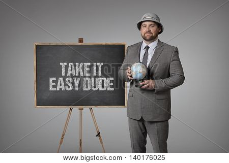 Take it easy dude text on blackboard with businessman holding globe in hands