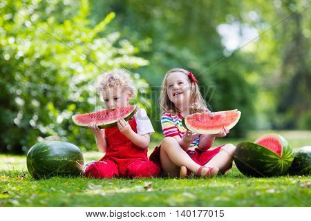 Child eating watermelon in the garden. Kids eat fruit outdoors. Healthy snack for children. Little girl and boy playing in the garden biting a slice of water melon.