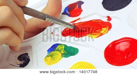 Mão com pincel e tintas na paleta