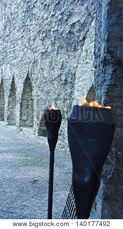 Fire in metal torch near estonian castle.