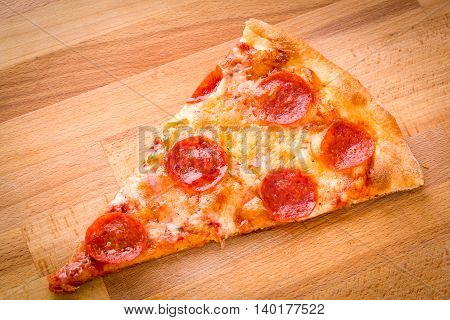 Slice of pepperoni pizza on a wood cutting board background