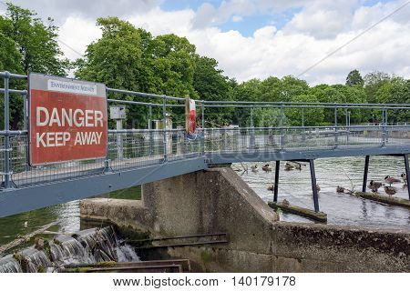 Pangbourne/UK. 10th July 2016. A Danger sign warns intruders of the dangers of trespassing on this weir on the River Thames at Pangbourne.