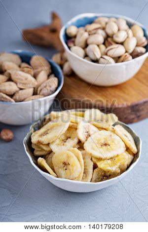 Banana chips, almonds and pistachios on a gray table