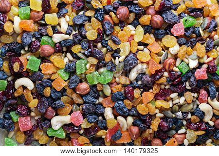 Mixed nuts and fruits background including raisins, pine nuts, cashews