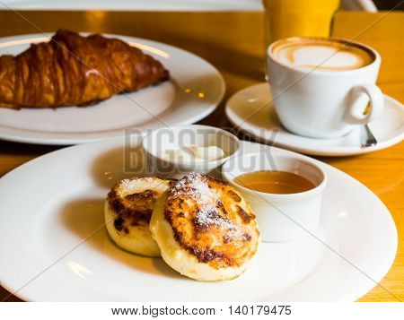 russian cheesecakes with a croissant and cappuccino in the table