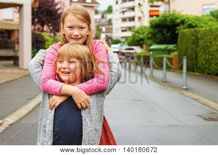 Outdoor portrait of a cute little boy and his sister hugging each other