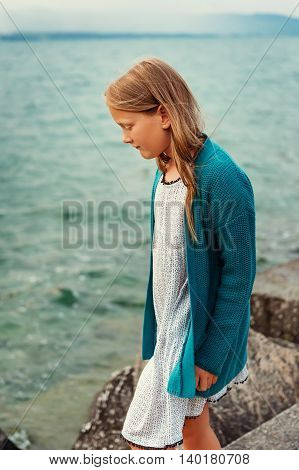 Adorable little girl of 8-9 years old playing by the lake, wearing white dress and blue knitted jacket