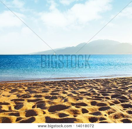 Sand on beach blue sky with airy clouds and sea