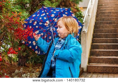 Cute toddler boy with umbrella playing outdoors on a rainy day, wearing blue jacket.