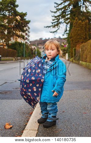 Cute toddler boy with umbrella playing outdoors on a rainy day, wearing blue jacket