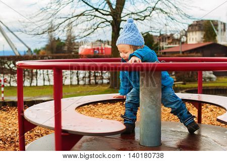 Little toddler boy having fun in the park on a cold autumn day
