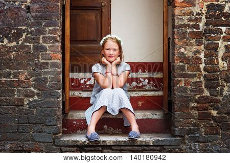 Outdoor fashion portrait of a cute little girl wearing black and white dress and grey shoes