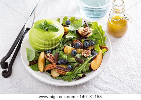 Fresh and healthy salad with vegetables, nuts and fruits