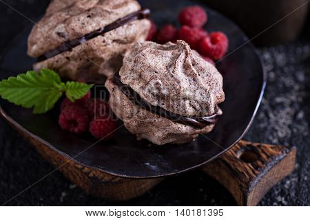 Meringue dessert with chocolate and raspberries on dark background