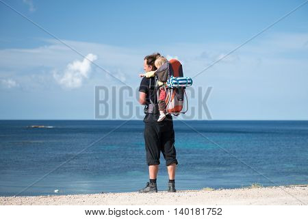 Father And Baby In Backpack Carrier Outdoors Near The Sea