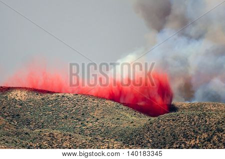 Red Fire Retardant Settling into Depression After Being Dropped on a Raging Wildfire