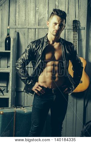 Handsome young man with sexy muscular bare torso in leather jacket standing with acoustic guitar and wine bottle on wooden background