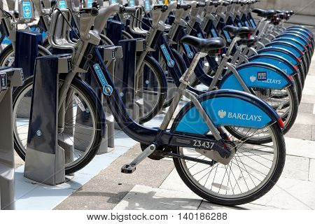 LONDON ENGLAND - JULY 1 2014: Shared bikes are lined up in the streets of London. Barclays Cycle Hires launched in July 2010 has over 720 stations and 10000 bikes throughout London.