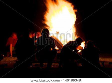 silhouette of people sitting in front of a campfire in the night.