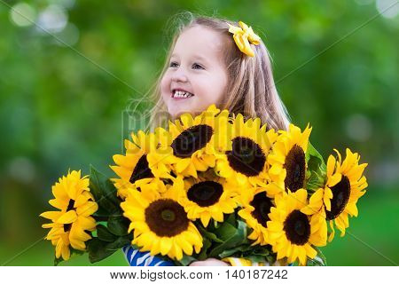 Happy laughing little girl holding sunflower bouquet. Child playing with sunflowers. Kids picking fresh sun flowers in the garden. Children gardening in summer. Outdoor fun for family.