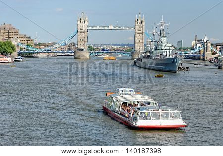 LONDON UNITED KINGDOM - JULY 1 2014: A City Cruises tour boat sails on the Thames River near Tower bridge. Thames is the longest river in England with 346 km (215 miles) long.