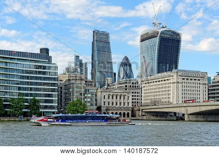 LONDON UNITED KINGDOM - JULY 1 2014: A City Cruises tour boat sails on the Thames River near London Bridge. Thames is the longest river in England with 346 km (215 miles) long.
