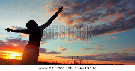 Woman standing on meadow with summer herbs over cloudy sky and sunset light