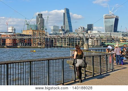 LONDON UK - JULY 1 2014: People enjoying a nice summer afternoon and the great view of the City at the riverside on the south bank of Thames river near the Millennium bridge.