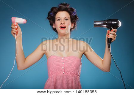 Young woman preparing to party having fun funny girl styling hair with two hairdreyers retro style on blue