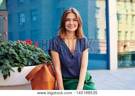 Portrait of beautiful young woman sitting on round bench in the city downtown on a warm sunny day