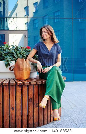 Elegantly dressed young beautiful woman is sitting on round bench with flower pot in the middle on mirror glass building background